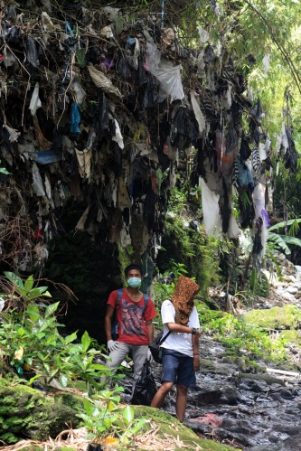 Bayu and Joan standing bellow the garbage stuck on the tree during flood caused by materials from the erruption
